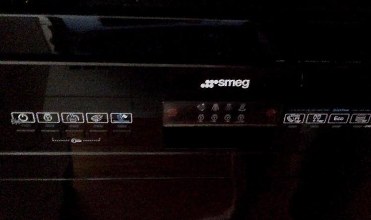 Black dishwasher panel with Smeg written on it.